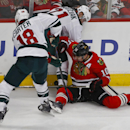 Chicago Blackhawks left wing Patrick Sharp (10) battles for the puck with Minnesota Wild center Ryan Carter (18) and center Kyle Brodziak (21) during the second period of an NHL hockey game in Chicago, Sunday, Jan. 11, 2015 The Associated Press