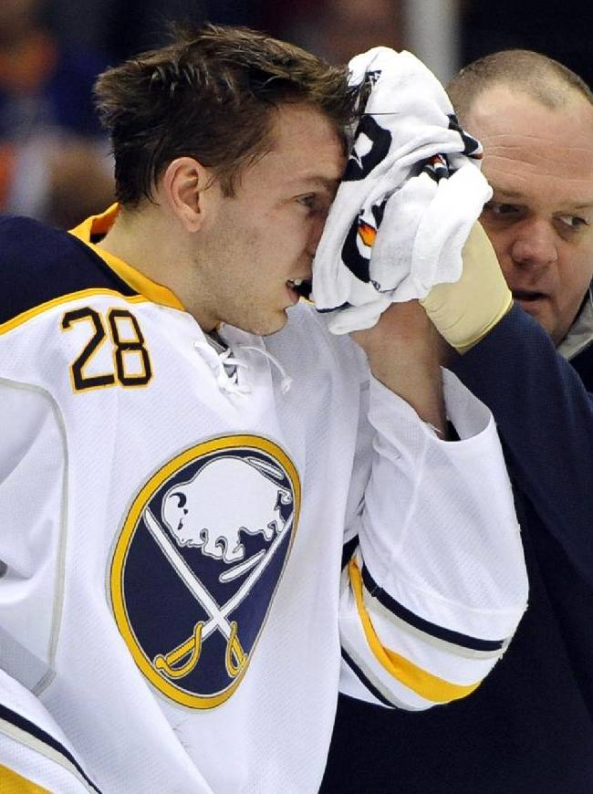 Buffalo Sabres' Zemgus Girgensons (28), of Latvia, is assisted off the ice after being injured in the first period of an NHL hockey game against the New York Islanders on Tuesday, Oct. 15, 2013, in Uniondale, N.Y