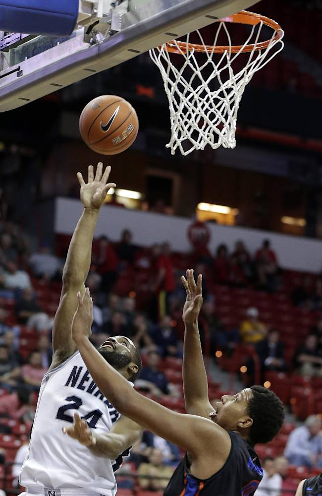 Boise State's Ryan Watkins covers a shot from Nevada's Deonte Burton during the second half of an NCAA college basketball game in the quarterfinals of the Mountain West Conference tournament Thursday, March 13, 2014, in Las Vegas. Boise State defeated Nevada 75-62