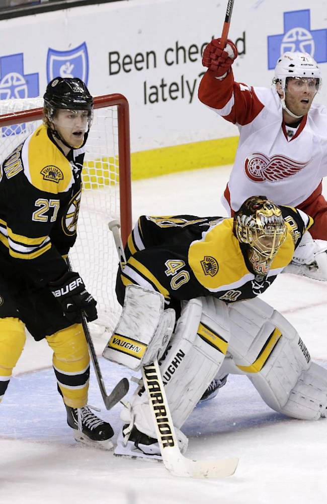 Detroit Red Wings forward Luke Glendening, right, looks for the shot as he positions himself behind Boston Bruins goalie Tuukka Rask (40), of Finland, and Bruins defenseman Dougie Hamilton (27) during the third period of an NHL hockey game on Saturday, Oct. 5, 2013, in Boston