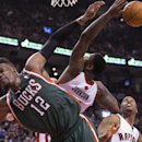 Toronto Raptors' Amir Johnson, center, battles for the ball with Milwaukee Bucks' Jeff Adrien, left, as Raptors' Kyle Lowry looks on during first half NBA basketball action in Toronto on Monday April 14, 2014 The Associated Press