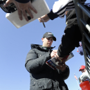 NASCAR driver Denny Hamlin signs autographs before practicing for Sunday's NASCAR auto race Friday, Feb. 27, 2015, in Hampton, Ga. (AP Photo/John Amis)