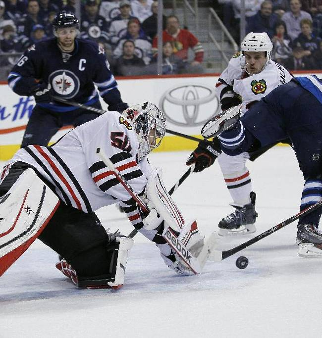 Chicago Blackhawks goaltender Corey Crawford (50) stops Winnipeg Jets' Bryan Little (18) backhander as Hawks' Niklas Hjalmarsson, second from right, and Jets' Andrew Ladd (16) look for the rebound during the second period of an NHL hockey game in Winnipeg, Manitoba on Thursday, Nov. 21, 2013