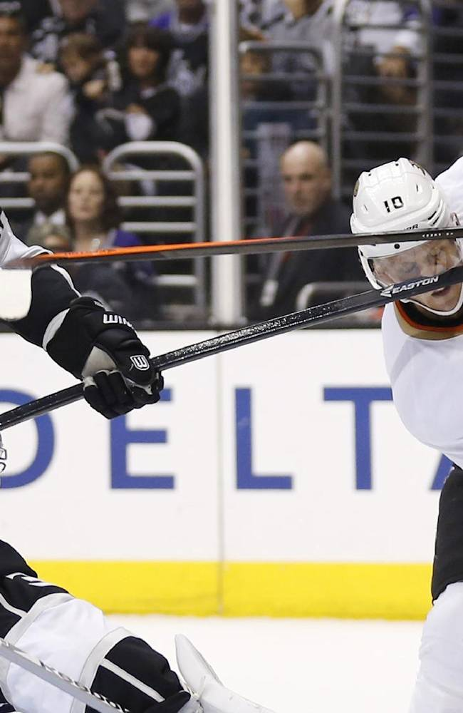 Anaheim Ducks right wing Corey Perry, right, loses his stick as he takes a stick to the face from Los Angeles Kings defenseman Robyn Regehr, left, as Los Angeles Kings goalie Martin Jones makes a save during the first period of an NHL hockey game in Los Angeles, Saturday, March 15, 2014