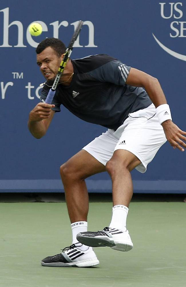 Jo-Wilfried Tsonga, from France, returns a volley to Mikhail Youzhny, from Russia, during a first round match at the Western & Southern Open tennis tournament, Tuesday, Aug. 12, 2014, in Mason, Ohio