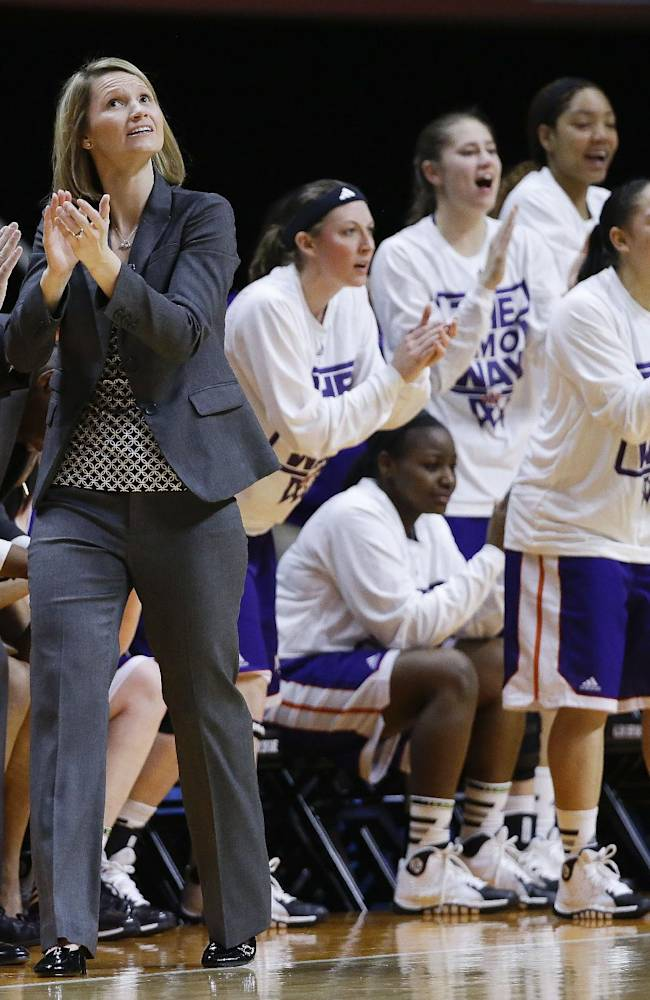 In this March 22, 2014 file photo, Northwestern State co-head coaches and spouses Scott Stoehr, left, and Brooke Stoehr celebrate a score against Tennessee in the first half of an NCAA women's college basketball first-round tournament game in Knoxville, Tenn. Of the thousands of NCAA athletic programs, an Associated Press survey found 13 that have spouses working as co-head coaches