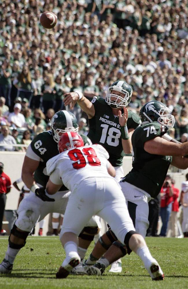 Michigan State quarterback Connor Cook (18) throws a pass as Michigan State's Blake Treadwell (64) blocks Youngstown State's D.J. Moss during the first quarter of an NCAA college football game, Saturday, Sept. 14, 2013, in East Lansing, Mich. Michigan State won 55-17