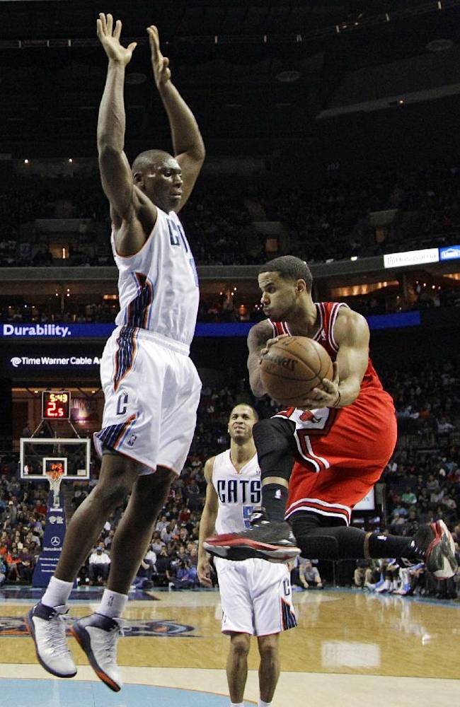 Chicago Bulls' D.J. Augustin, right, looks to pass around Charlotte Bobcats' Bismack Biyombo, left, during the first half of an NBA basketball game in Charlotte, N.C., Saturday, Jan. 25, 2014