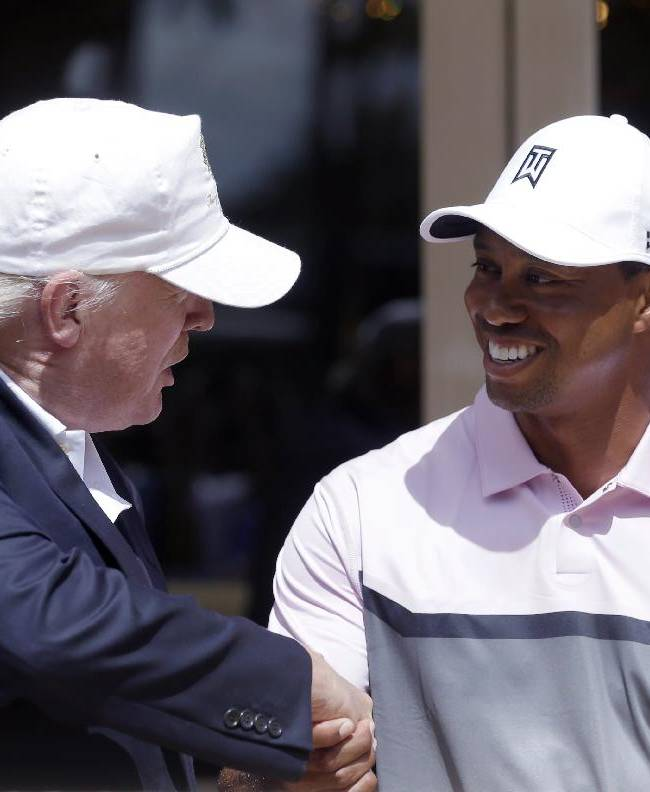 Donald Trump, left, shakes hands with Tiger Woods during a ribbon cutting for the new Tiger Woods Villa at the Trump National Doral golf course, Wednesday, March 5, 2014 in Doral, Fla
