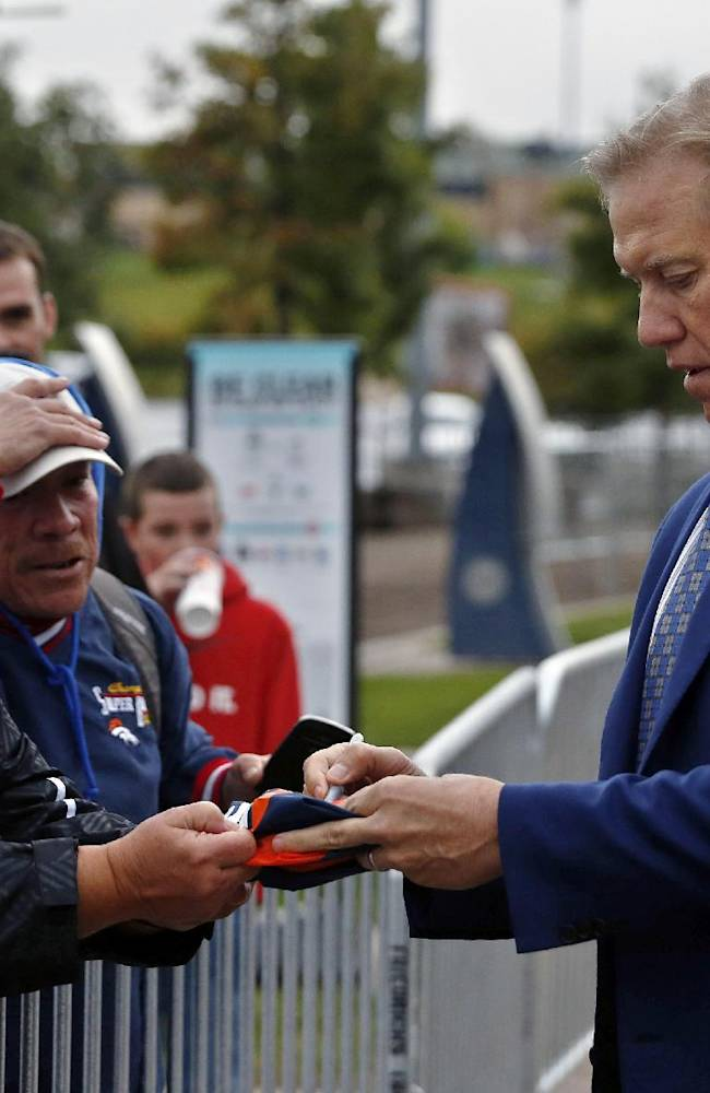 Denver Broncos executive vice president John Elway, a former quarterback for the NFL football team, signs autographs for fans as he arrives to the unveiling ceremony for the Broncos Ring of Fame Plaza, at Mile High Stadium in Denver on Friday, Sept. 27, 2013