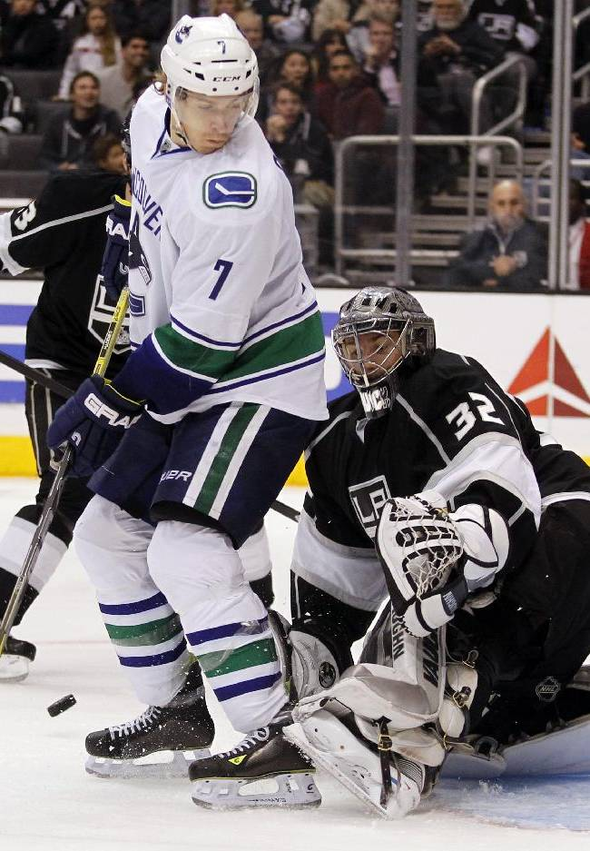 Vancouver Canucks left wing David Booth (7) and Los Angeles Kings goalie Jonathan Quick (32) look for the puck on a shot during the third period of an NHL hockey game Saturday, Jan. 4, 2014, in Los Angeles. Kings won 3-1