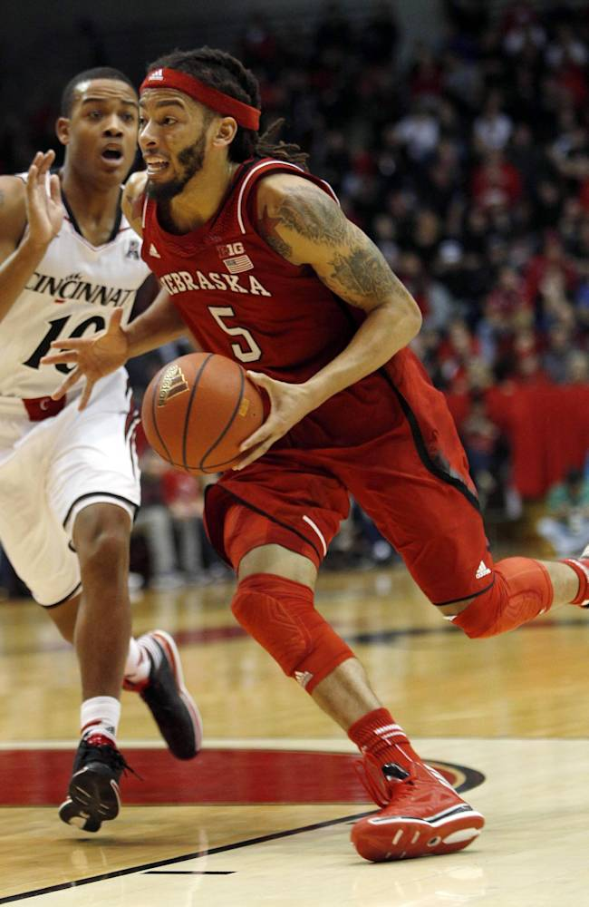 Nebraska guard Terran Petteway (5) drives to the basket against Cincinnati guard Troy Caupain (10) during the second half of an NCAA college basketball, Saturday, Dec. 28, 2013, in Cincinnati. Cincinnati won 74-59