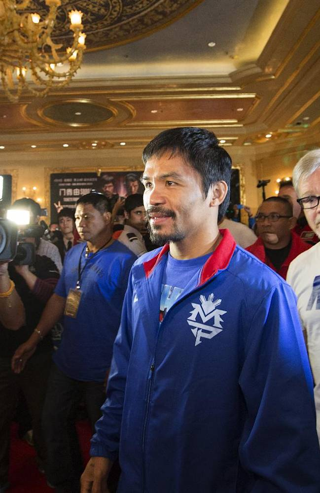 In this Tuesday, Nov. 19, 2013 photo released by the Venetian Macao, Filipino boxer Manny Pacquiao, center, accompanied by his trainer Freddie Roach, right, arrives at the main lobby of the Venetian Macao in Macau. Pacquiao and Brandon Rios of the United States are scheduled to fight in their welterweight match at the casino on Nov. 24