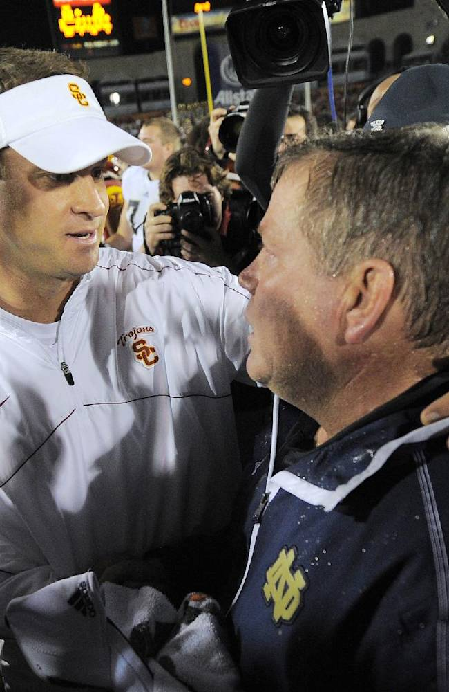 In this Nov. 24, 2012, file photo, Southern California coach Lane Kiffen, left, shakes hands with Notre Dame coach Brian Kelly after Notre Dame defeated Southern California 22-13 in an NCAA college football game in Los Angeles. While at least one team has been ranked in 64 of the 75 meetings since The Associated Press started the poll in 1936, this season marks the third time in the past four years where neither has been ranked