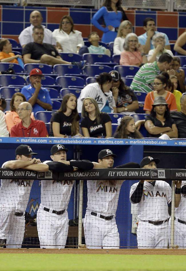 The Miami Marlins bench and fans watch the final minutes of an interleague baseball game against the Detroit Tigers in the tenth inning on Saturday, Sept. 28, 2013, in Miami. The Marlins won 2-1