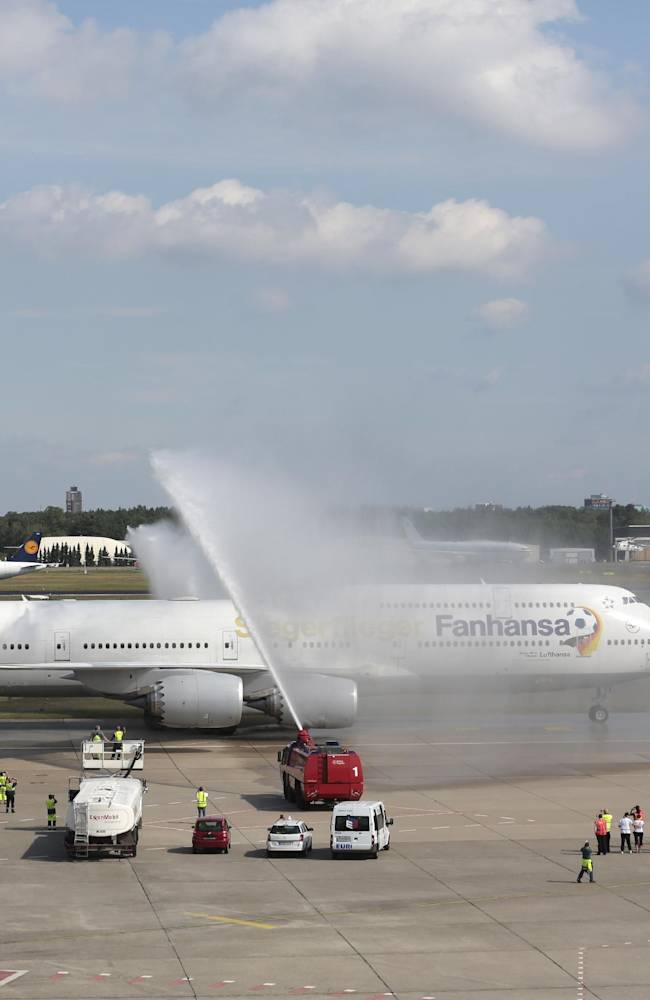 The plane with the players of German national soccer team  arrives at Tegel airport in Berlin Tuesday, July 15, 2014.  Germany's World Cup-winning team has returned home from Brazil to celebrate the country's fourth title with huge crowds of fans. The team's Boeing 747 touched down at Berlin's Tegel airport midmorning Tuesday after flying a lap of honor over the