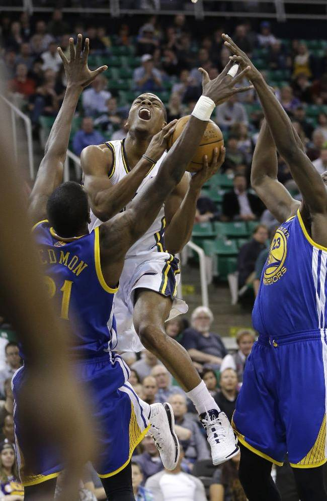 Utah Jazz's Alec Burks, center, drives to the basket as Golden State Warriors' Dewayne Dedmon, left, and Draymond Green (23) defend in the second half during an NBA preseason basketball game Tuesday, Oct. 8, 2013, in Salt Lake City. The Jazz won 101-78