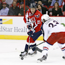 Washington Capitals center Brooks Laich (21) reaches for the puck with Columbus Blue Jackets center Brian Gibbons (23) in the second period of an NHL hockey game, Thursday, Dec. 11, 2014, in Washington The Associated Press