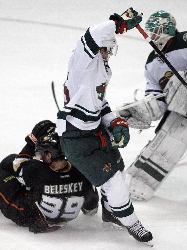 Anaheim Ducks left wing Matt Beleskey (39) gets upended by Minnesota Wild defenseman Jonas Brodin, center, of Sweden, as goalie Josh Harding, right, blocks the shot in the third period of an NHL hockey game Wednesday, Dec. 11, 2013 in Anaheim, Calif. Ducks won 2-1
