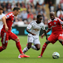 Swansea City's Nathan Dyer, center, skips over tackles from West Bromwich Albion's Youssuf Mulumbu, right, and Jason Davidson during their English Premier League soccer match at the Liberty Stadium, Swansea, Wales, Saturday, Aug. 30, 2014