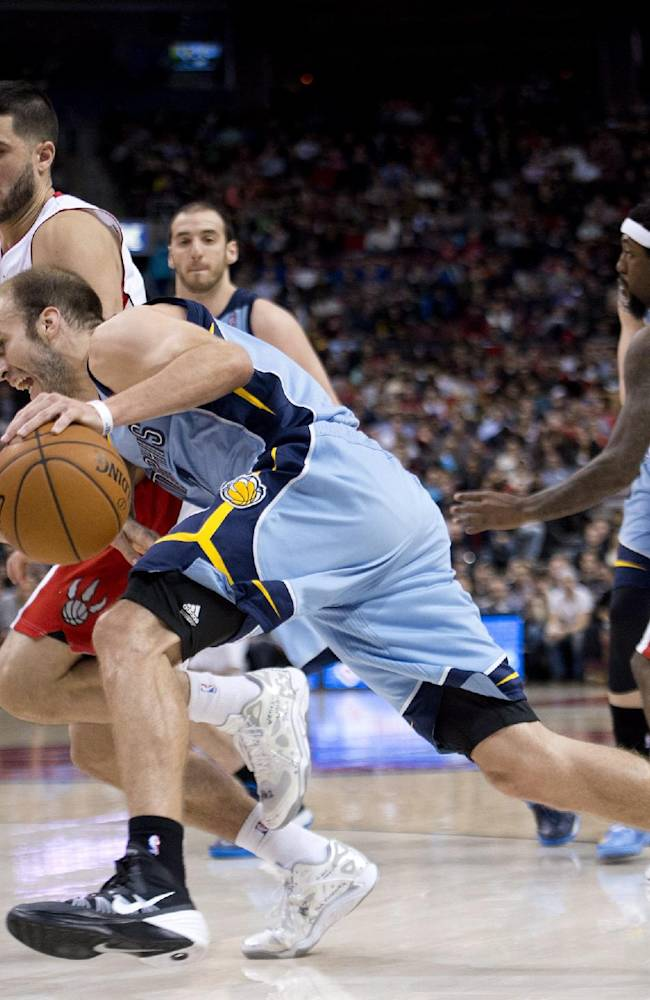 Memphis Grizzlies guard Nick Calathes, front, drives the ball to the net against the Toronto Raptors during second half NBA basketball action in Toronto on Friday, March. 14, 2014