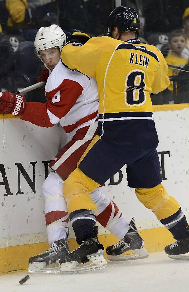 Nashville Predators defenseman Kevin Klein (8) checks Detroit Red Wings left wing Justin Abdelkader (8) into the boards while going for the puck in the first period of an NHL hockey game on Monday, Dec. 30, 2013, in Nashville, Tenn