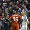 Liverpool's Mario Balotelli, centre, and Swansea's Jonjo Shelvey are spoken to by referee Keith Stroud, during the English League Cup soccer match between Liverpool and Swansea at Anfield Stadium, Liverpool, England, Tuesday Oct. 28, 2014