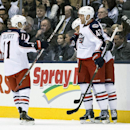 Columbus Blue Jackets Dalton Prout, right, celebrates with Derek MacKenzie, center, and Matt Calvert after Prout scored a goal against the Toronto Maple Leafs during the second period of an NHL hockey game in Toronto on Monday, March 3, 2014 The Associate
