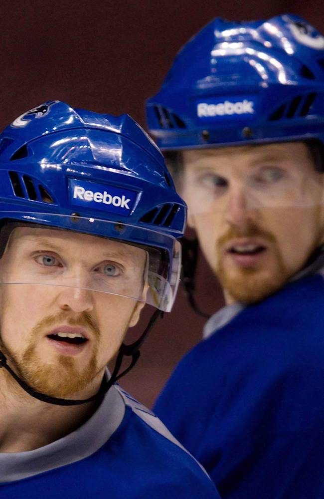 In this April 12, 2011, file photo, Henrik Sedin, left, and his twin brother Daniel Sedin look on during NHL hockey practice in Vancouver, British Coumbia. The twin superstarssigned four-year contract extensions with the Canucks. the team announced Friday, Nov. 1, 2013