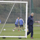 Arsenal's manager Arsene Wenger help to move a goal post during a training session at their London Colney training ground, Monday, March 10, 2014. Arsenal will play in a Champions League last sixteen second leg soccer match against Munich in Germany on Tu