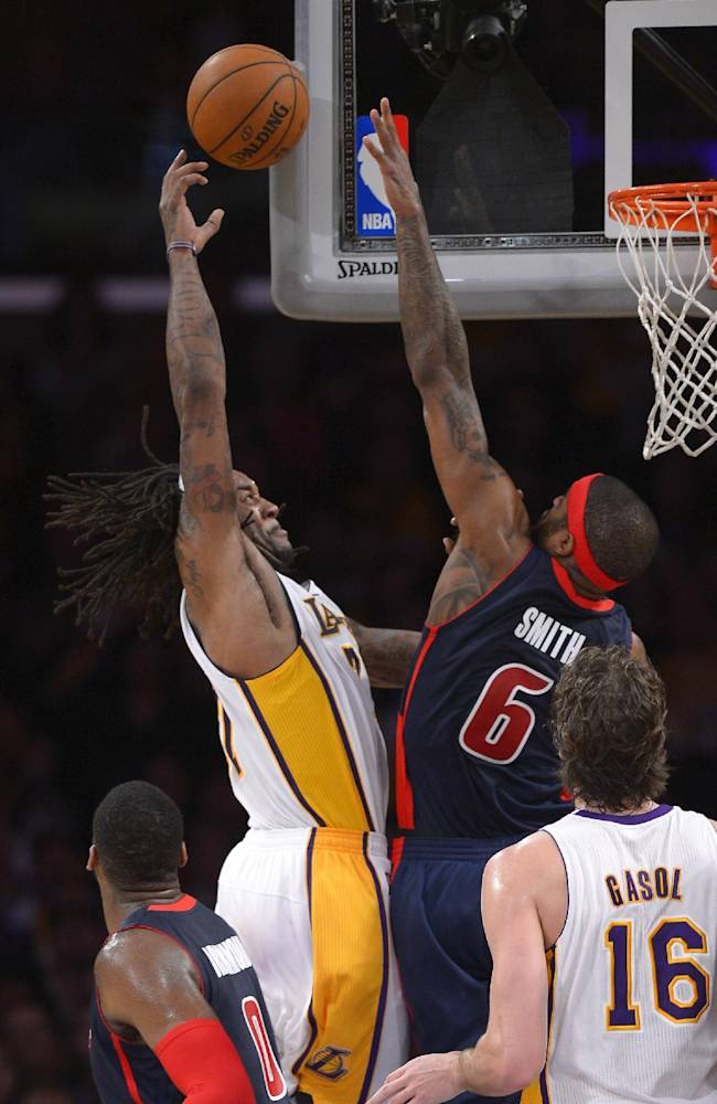 Los Angeles Lakers center Jordan Hill, left, puts up a shot as Detroit Pistons forward Josh Smith defends and center Pau Gasol, of Spain, stands by during the second half of an NBA basketball game Sunday, Nov. 17, 2013, in Los Angeles