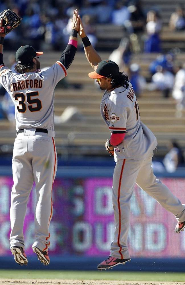 San Francisco Giants shortstop Brandon Crawford (35) celebrates with center fielder Angel Pagan, right, after defeating the Los Angeles Dodgers 7-4 in a baseball game in 10 inning on Sunday, May 11, 2014, in Los Angeles