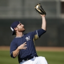 Milwaukee Brewers' Jonathan Lucroy makes a leaping catch on a pop fly during Brewers spring training baseball practice, Thursday, Feb. 20, 2014, in Phoenix The Associated Press