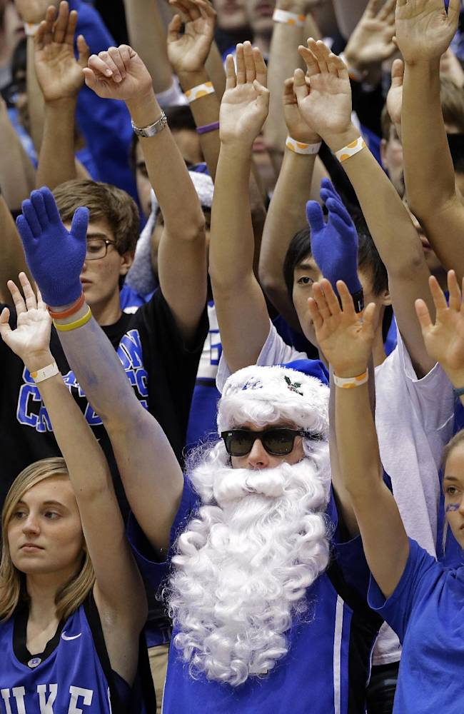 Duke fans raise their hands during the first half of an NCAA college basketball game against Vermont in Durham, N.C., Sunday, Nov. 24, 2013