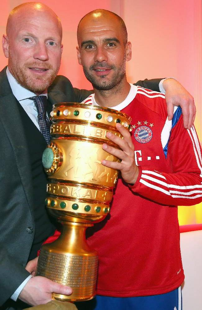 In this picture taken  Saturday May 17, 2014, Bayern Munich's coach Pep Guardiola, right, holds the German soccer cup with sporting director  Matthias Sammer during the after-match party after the club won the German soccer cup final  against Borussia Dortmund in Berlin