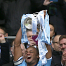 Manchester City's Vincent Kompany lifts the winners trophy after his team's 3-1 win against Sunderland during the League Cup Final at Wembley Stadium, London, England, Sunday March 2, 2014