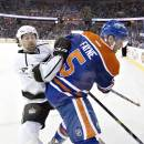 Los Angeles Kings' Justin Williams (14) checks Edmonton Oilers' Mark Fayne (5) during the first period of an NHL hockey game in Edmonton, Alberta, Tuesday, March 3, 2015. (AP Photo/The Canadian Press, Jason Franson)