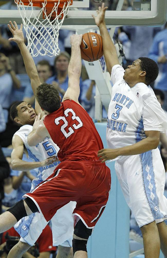 North Carolina's Marcus Paige, left, and Kennedy Meeks (3) stop Davidson's Tom Droney (23) short of the basket during the second half of an NCAA college basketball game in Chapel Hill, N.C., Saturday, Dec. 21, 2013. North Carolina won 97-85 in overtime