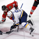 Chicago Blackhawks right wing Ben Smith (28) and St. Louis Blues center Steve Ott battle for a face-off in the Blackhawks' zone during the second period of an NHL hockey game Wednesday, Dec. 3, 2014, in Chicago The Associated Press