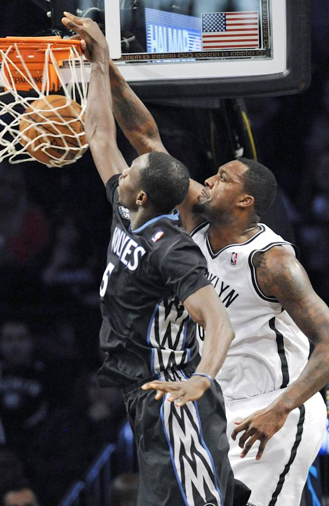 Brooklyn Nets' Andray Blatche, right, dunks the ball as he gets by Minnesota Timberwolves' Gorgui Dieng during the third quarter of an NBA basketball game Sunday, March 30, 2014, at Barclay's Center in New York. The Nets won 114-99