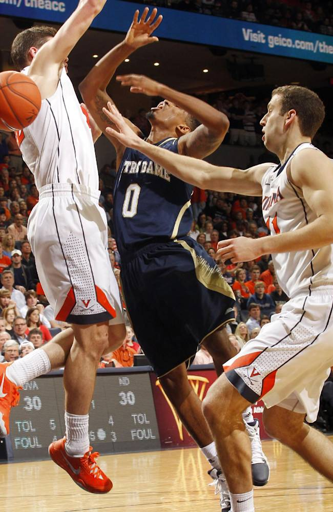Notre Dame guard Eric Atkins (0) is fouled by Virginia forward Evan Nolte, right, during an NCAA college basketball game Saturday, Feb. 22, 2014, in Charlottesville, Va