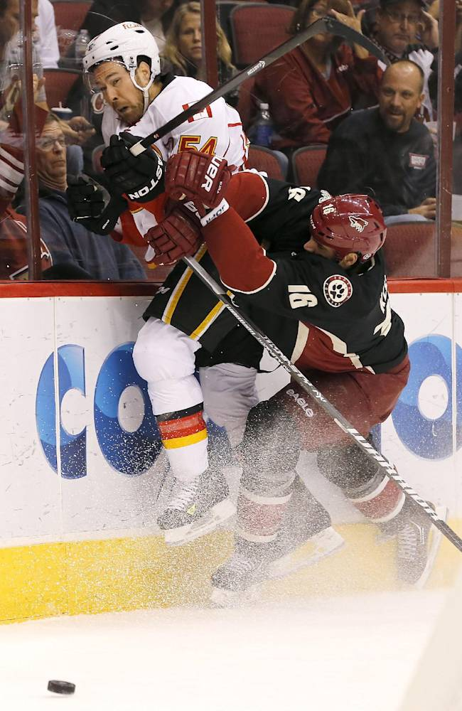 Phoenix Coyotes' Rostislav Klesla (16), of the Czech Republic, checks Calgary Flames' David Jones (54) into the boards during the first period of an NHL hockey game on Tuesday Oct. 22, 2013, in Glendale, Ariz