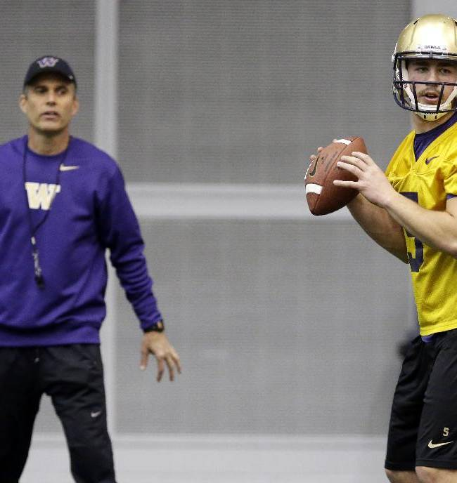 New Washington head football coach Chris Petersen, left, stands near redshirt quarterback Jeff Lindquist, right, as Lindquist passes on the first day of spring NCAA college football practice, Tuesday, March 4, 2014, in Seattle