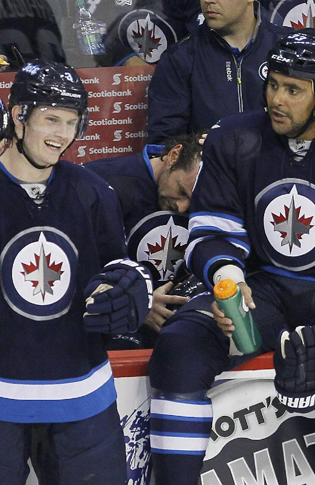 Winnipeg Jets' Jacob Trouba (3) and Dustin Byfuglien (33) joke around during a commercial break during the first period of a preseason NHL hockey game against the Boston Bruins on Thursday, Sept. 26, 2013, in Winnipeg, Manitoba