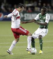 New York Red Bulls forward Fabian Espindola, left, and Portland Timbers midfielder Diego Chara battle over the ball during the second half of an MLS soccer game in Portland, Ore., Sunday, March 3, 2013. Portland and New York tied 3-3.(AP Photo/Don Ryan)