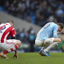 Manchester City's Edin Dzeko, right, and Stoke's Marc Wilson squat on the pitch after their English Premier League soccer match at the Etihad Stadium, Manchester, England, Saturday Feb. 22, 2014. Although Manchester City won the game 1-0 Dzeko missed a la
