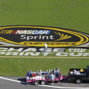 FILE - In this Oct. 10, 2012, file photo, workers paint a logo on the grass near the front stretch during preparation for a NASCAR Sprint Cup Series auto race in Concord, N.C. Sprint informed NASCAR it won't extend title sponsorship of the top Sprint Cup Series beyond its current contract, which expires after the 2016 season.