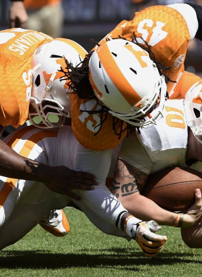 Tennessee quarterback Riley Ferguson (10) is stopped by linebackers A.J. Johnson (45) and Owen Williams (58) during the Orange and White game at Neyland Stadium in Knoxville, Tenn., Saturday, April 12, 2014