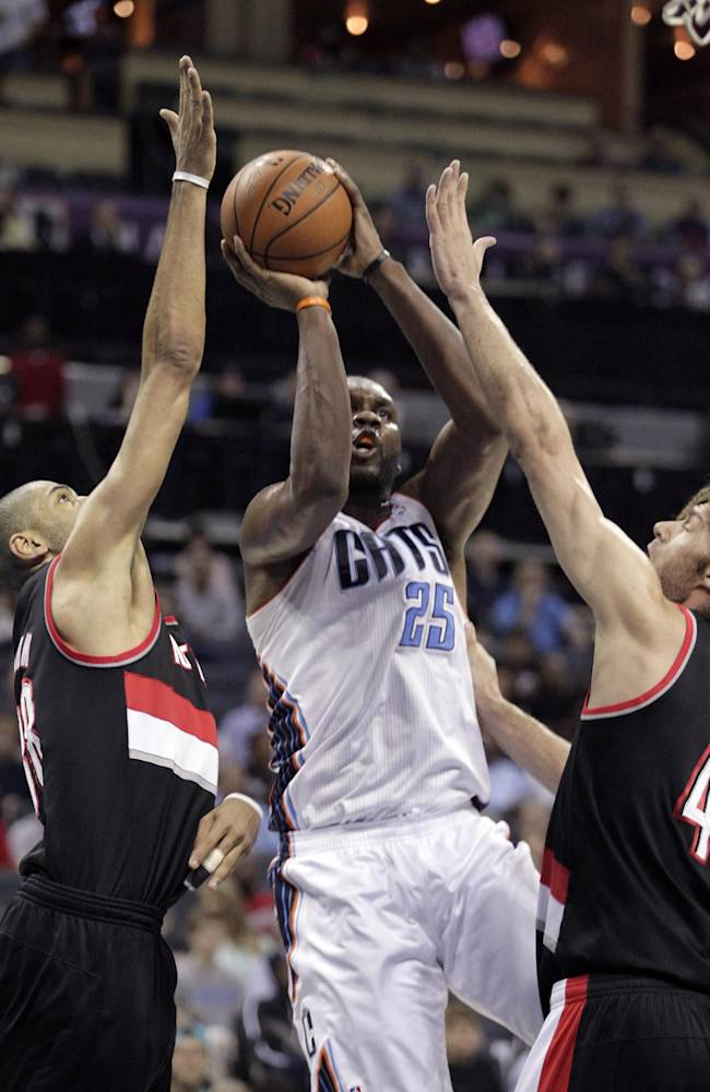 Charlotte Bobcats' Al Jefferson, middle, aims his short jumper through the defense of Portland Trail Blazers' Nicolas Batum, left, and Robin Lopez, right, during the first half of an NBA basketball game in Charlotte, N.C., Saturday, March 22, 2014
