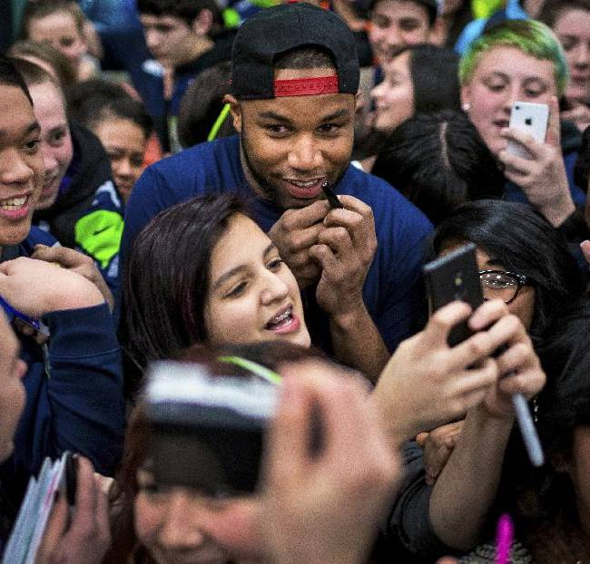 Seattle Seahawks wide receiver Golden Tate, center, is mobbed by hundreds of students at Auburn Riverside High School after the institution won the Verizon-sponsored second annual